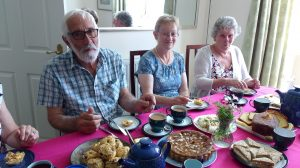 Man and two women at a table eating afternoon tea
