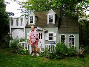Devizes U3A member standing front of a miniature house