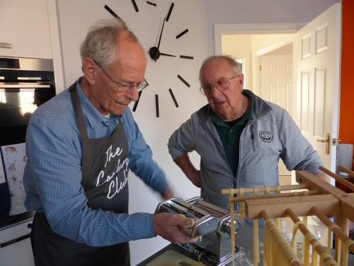 Two men making pasta